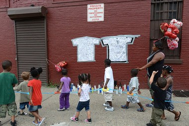 Children pass by a memorial for Lawrence Campbell, the man who was killed by police after he fatally shot Police Officer Melvin Santiago on July 13, which has been put up on Grant Avenue near Martin Luther King Drive, Monday, July 14, 2014. Reena Rose Sibayan/The Jersey Jourrnal