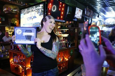Bartender Robin Myers proudly displays the certificate proclaiming the Corner Bar Jersey's best bar (Saed Hindash I NJ Advance Media for NJ.com)