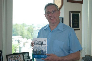 "Freeholder Bill O'Dea poses with a copy of his book, ""The Legacy of Haguesville."""