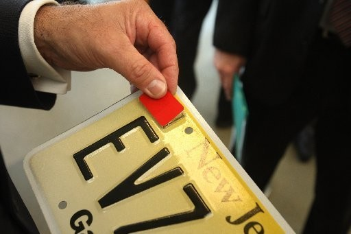 A red decal attached to a license plate at a press conference announcing the specifics of Kyleigh's Law. Probationary drivers under the age of 21 are required to affix a red decal on their license plates.