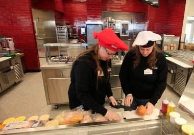 Twin sisters Vanessa and Samantha Silverman make a sandwich at the new Kearny store.
