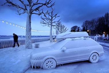 A man walks past an ice covered car on the frozen waterside promenade at Lake Geneva in the city Versoix, near Geneva on early February 5, 2012.