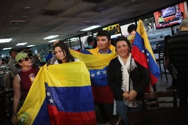 People hold Venezuelan flags as they listen to television sets reporting on the death of Venezuelan president Hugo Chavez Tuesday in Doral, Fla.