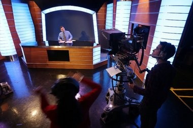 """TJ Russell delivers the news during an """"Introduction to Control Room and Studio Production"""" class at Montclair State University's DuMont Media Center in Montclair. The university's new communications school is forming a partnership with six New Jersey media organizaitions."""