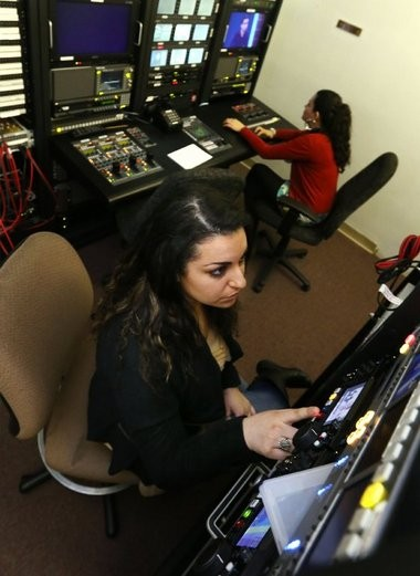 """Gabrielle Terkhanian, foreground, and Stefani Gore work the control room during the newscast for """"Introduction to Control Room and Studio Production"""" at Montclair State University's DuMont Media Center."""