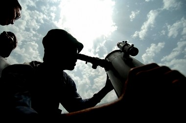 An Indian volunteeer of the Amateur Astronomer Association is sillhouetted against the sky as he adjusts a telescope to view the rare celestial event at the Nehru Centre Planetarium in New Delhi. A land board in Hawaii has approved a plan to construct the world's largest telescope.