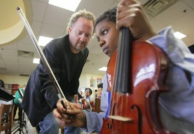 Conductor Jeffrey Grogan helps 10-year-old Justice Thompson, a student at University Heights Charter School in Newark, with his fingering.