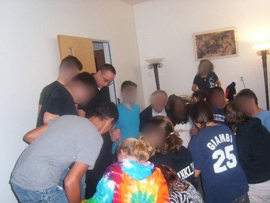 The Rev. Michael Fugee participates in a prayer circle with teens and adults during a pilgrimage to Canada in 2010. It was trips like these led to his being charged with violating a court order.