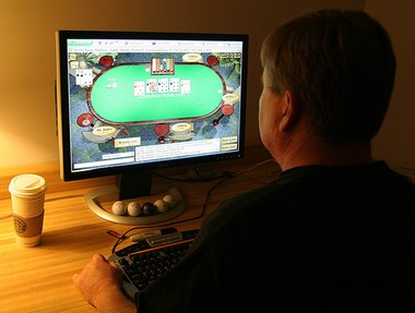 A man plays poker on his computer connected to an internet gaming site from his home in Manassas, Va., in this file photo.