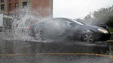A car drives through the rain on Washington Street in Newark on Monday. Another day of heavy rain is expected.