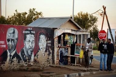 People walk past a mural of Nelson Mandela in Soweto. Similar murals are seen across the country.