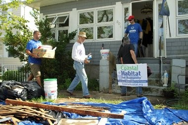 Vince Darago (center, with hat) walks into his Sandy damaged Manasquan home with volunteers from Allstate earlier this month.