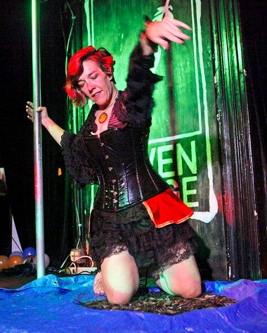 Gypsy Lavery of Karnevil Circus Sideshow kneels into a pile of broken glass during a twisted carnival and burlesque performance at the Raven Lounge in Philadelphia, PA