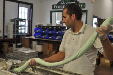 Darko Tushev feeds taffy into the cutting/wrapping machine at Shriver's.
