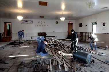 Volunteers clean and strip the floors of mold and dirt at a church on Florence Avenue in Union Beach last November.