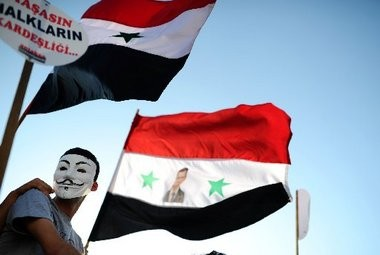 A protester waves a Syrian flag with the photograph of Syrian President Bashar al-Assad during a rally in Hatay, Syria, against a possible attack on Syria in response to alleged use of chemical weapons by the Assad government. Members of the House and Senate were briefed in Washington today on evidence of the Assad regime's use of chemical weapons.