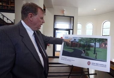 New Brunswick Theological Seminary President Gregg Mast points to a poster depicting the new seminary building. The school's financial struggles forced the it to sell part of its campus to neighboring Rutgers University. Now, the seminary is breaking ground on a major building project designed to revitalize the nation's oldest Presbyterian seminary.