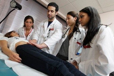Yinzhu Shen, 30, of Newark, is examined by medical students at Rutgers New Jersey Medical School Student Family Health Care Center in Newark. Obamacare is expected to generate more patients and more medical jobs.