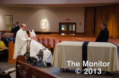 The Rev. Matthew Riedlinger pushes retired Trenton Bishop John M. Smith in his wheelchair during a priest's funeral in Burlington County earlier this month. The diocese said Riedlinger was given special permission to wear clerical garb in public to help Smith. The photo was on the public website of The Monitor, a publication of the diocese.