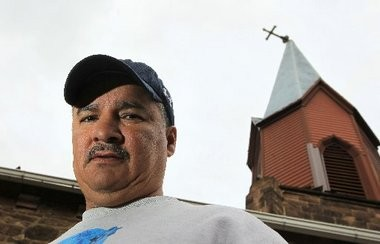 Miguel Ortiz, pastor of La Senda Antigua, stands on a lower roof of the historic Belleville church his congregation now owns.