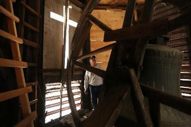 Pastor Miguel Ortiz in the damaged belfry of his Belleville church, next to its original bell.