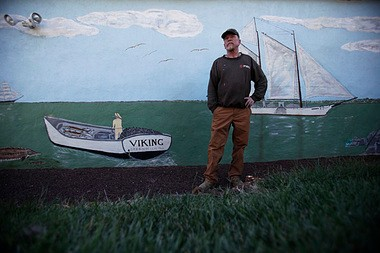 "Martin ""Reds"" Morse stands beside the mural he painted on the exterior of his garage depicting a local lighthouse, an oyster schooner and the 100-year-old shad boat ""Viking"" he keeps in his front yard in Greenwich, Cumberland County."