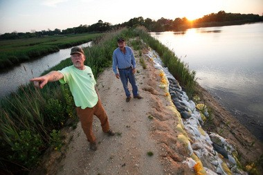 "Ed ""Shep"" Sheppard and Martin ""Reds"" Morse walk along Mill Creek Dike in Greenwich, Cumberland County. Many locals fear the dike will be taken out by the next big storm."