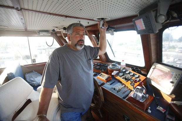 Capt. Mike Rothamn at the helm of the Bonanza II fishing boat at the docks of Higbees Marina in the small Cumberland County fishing village of Fortescue, which was badly damaged by Hurricane Sandy last year.