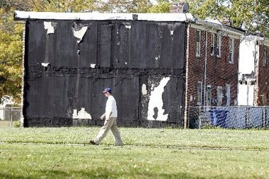 A man walks past a home in the Mount Holly Gardens section of Mount Holly. The attached neighboring home has been razed, leaving a wall of tar exposed.