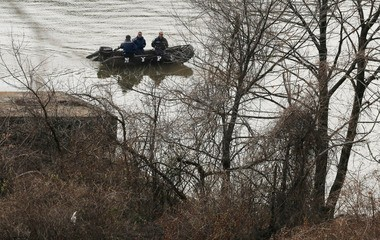 NYPD personnel use search the shoreline as emergency personnel investigate a Metro-North passenger train derailment in the Bronx.