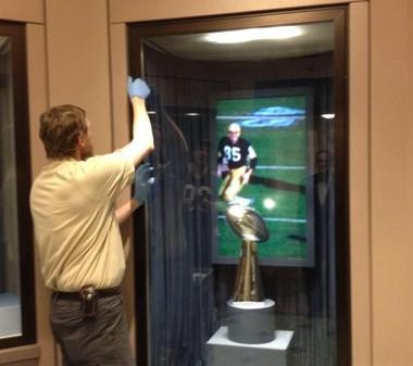 Exhibit preparer Seth Goodwin puts the original Vince Lombardi trophy in a display case at Newark museum.