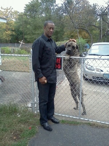 Trigger and owner Paul Clarke pose for a photo outside their Paterson home.
