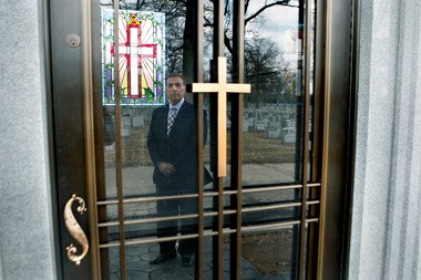Headstone dealer Ralph Rullis, 65, is seen in the reflection of a door to a mausoleum installed by the Archdiocese of Newark at Gate of Heaven Cemetery in East Hanover.