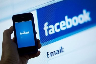 File photo of an Apple iPhone displaying the Facebook app. A new report from the Pew Research Center tracks how Facebook, Twitter and other social media sites are changing the way users get their news.