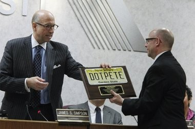 Simpson, who would pepper his transportation speeches with a heavy dose of humor, presents a plaque to longtime Department of Transportation staffer Peter Busichio during a meeting in March.