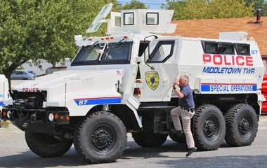 Middletown Police SFC William Colangelo climbs into the cab of the department's mine-resistant armored vehicle acquired last year through the government's military surplus program for high-water rescues. (Tony Kurdzuk | NJ Advance Media)