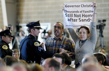 Police remove Hurricane Sandy victims Joe Mangino and Amanda Devecka-Rinear as New Jersey Gov. Chris Christie speaks during the Iowa Agriculture Summit, Sat., March 7, 2015, in Des Moines, Iowa.
