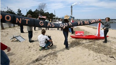 Members of the Sierra Club and other environmental groups hold banners during an Earth Day rally on the beach in Beesleys Point in Upper Township, N.J., Tuesday, April 22, 2014, to protest the proposed pipeline through the pinelands and continued pollution from the BL England power plant, seen in background. (AP Photo/The Press of Atlantic City, Dale Gerhard/)
