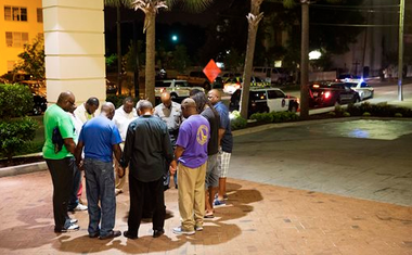 Worshippers gather to pray in a hotel parking lot across the street from the scene of a fatal shooting at a church Wednesday in Charleston, S.C. Nine people, including the pastor, were killed.