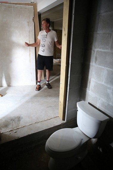 Steve Burkhardt of Toms River shows off the toilet that is being kept in the elevator shaft (minus the elevator) that is still incomplete more than 900 days since he hired a builder to replace his Sandy-ravaged home on Barnegat Bay.