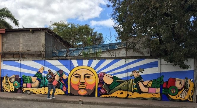 With a child on his shoulders, a man walks by one of many religious-themed murals in downtown Esteli. (Mark Mueller | NJ Advance Media for NJ.com)