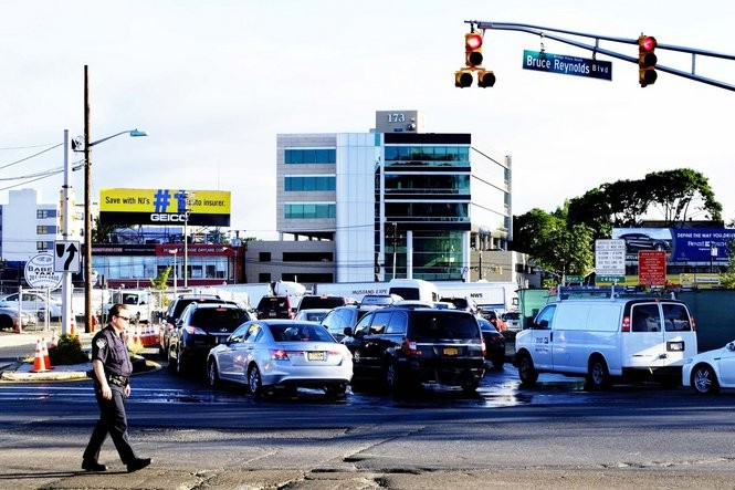 A member of the Port Authority Police Department monitors traffic entering the lanes that lead to the George Washington Bridge toll plaza in Fort Lee. (Aristide Economopoulos | NJ Advance Media, for NJ.com)