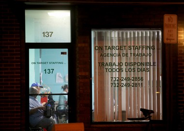 """Temp workers sit inside On Target Staffing, an employment agency in New Brunswick, before dawn. The agency is one of more than a dozen temp firms in the city. """"Work available every day,"""" the sign in the window says in Spanish. (Ed Murray 