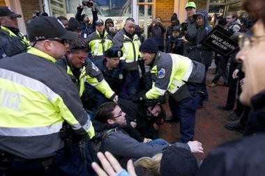 Police try to remove demonstrators from attempting to block people entering a security checkpoint, Friday, Jan. 20, 2017, ahead of President-elect Donald Trump's inauguration in Washington.