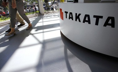 In this May 4, 2016, file photo, visitors walk by a Takata Corp. desk at an automaker's showroom in Tokyo.