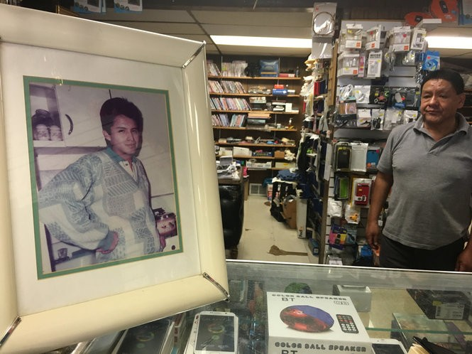 Miguel Victoria, right, takes down an undated family photo of Tito Merino from a wall inside Victoria Audio and Video in Paterson to show a reporter in July of 2017.
