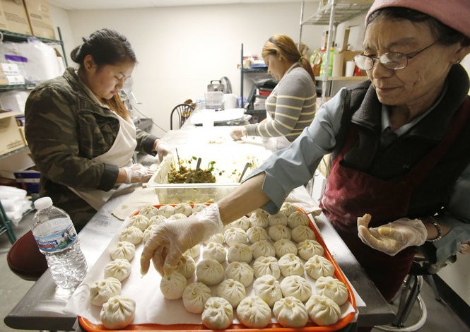 Pema Yanzon, right, places a momo dumpling on a tray at a restaurant in Columbus popular both with immigrants and native Ohioans. Yanzon, age 62, came to this country from Tibet in 2008. (Martha Irvine | AP Photo)