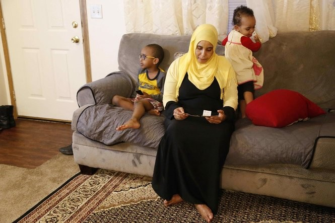 Amina Olow, a refugee from Somalia, looks at photos of two of her eldest daughters while siting with two of her other children in her Columbus home. (Martha Irvine | AP Photo)