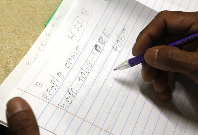 Man Sing Sutam, a 48-year-old refugee from Bhutan, practices writing in English during a U.S. citizenship class. (Martha Irvine | AP Photo)