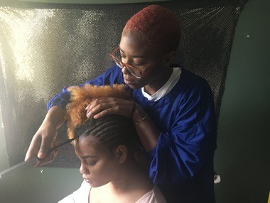 Tiana Francis, of Paterson, styles a client's hair in cornrows.